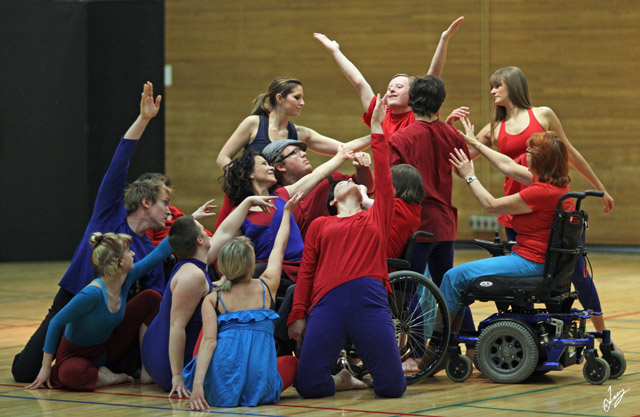 Picture of a large group of CRIPSiE dancers in blue and red all crowded together and reaching towards one dancer in the middle. Some dancers are standing, some kneeling, some sitting in wheelchairs,
