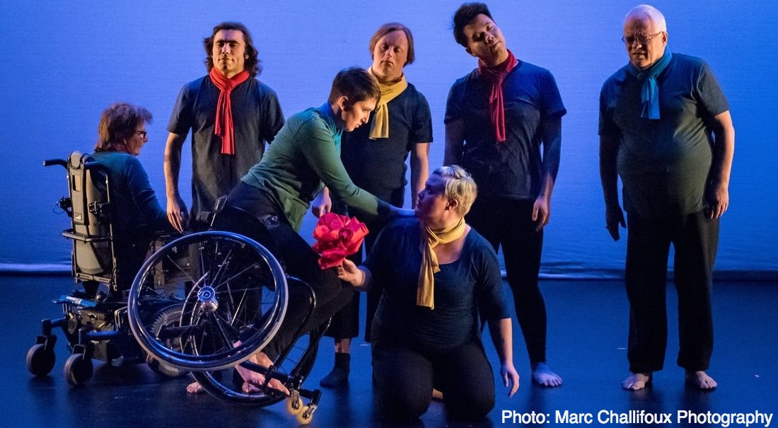 four CRIPSiE dancers sway gently in the blue-washed background. Once dancer steers her power chair around them. A sixth dancer tilts up on their manual chair wheel balancing against a seventh dancer, kneeling on the ground holding a big red rose