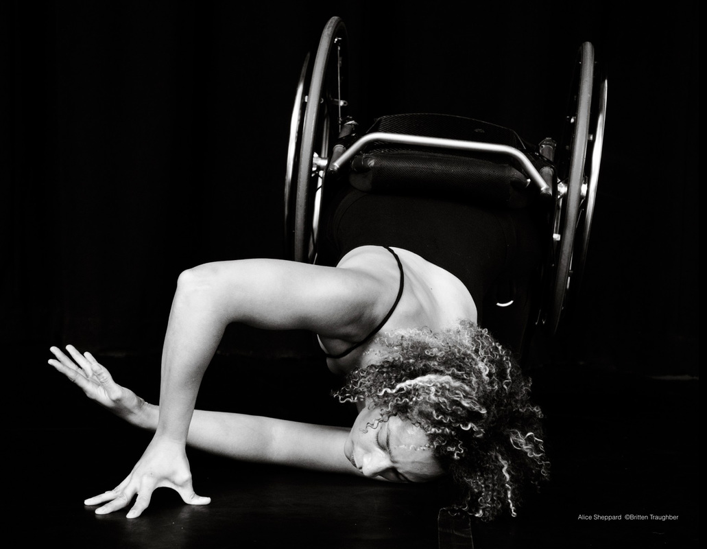 Black and white Photo of Alice Sheppard rolling on the ground, dancing with her wheelchair